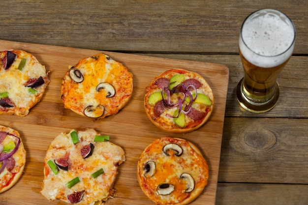 ビールのグラスを木の板で提供するおいしいピザ