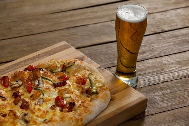Вкусная пицца подается на деревянной доске с бокалом пива