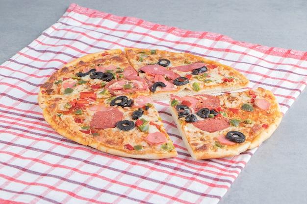 Deliziosa pizza su un asciugamano su marmo