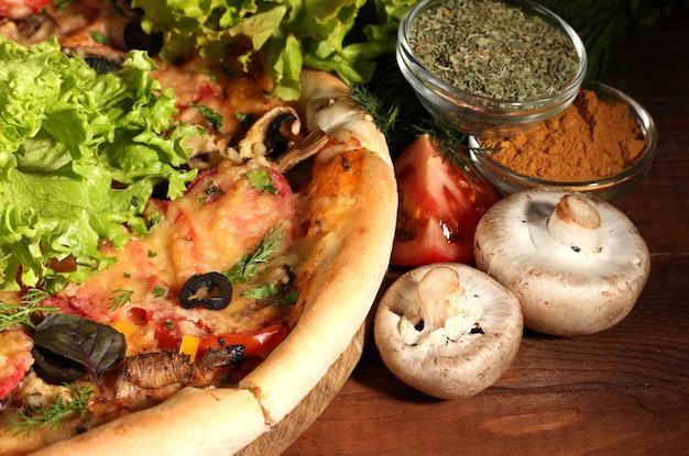 茶色の表面の木製テーブルにおいしいピザ、野菜、スパイス
