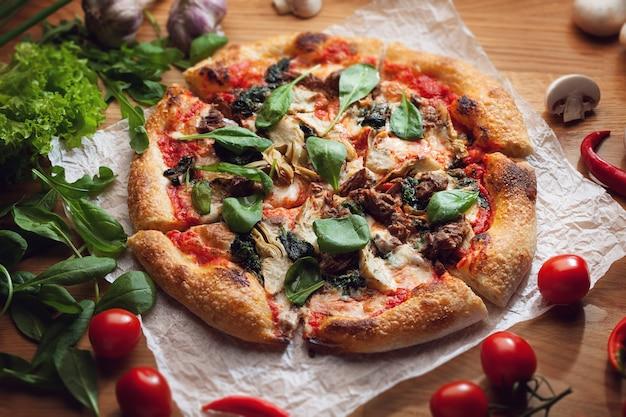 アーティチョークとマグロのおいしいピザを木製のテーブルでお召し上がりいただけます