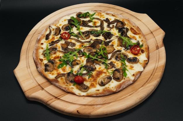 ルッコラとトマトをボードに乗せたおいしいピザ