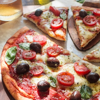 Delicious pizza with cheese and cherry tomato slices on wooden table