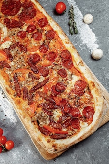 Delicious pizza with chicken fillet, ham, bacon, sausages, tomato sauce and mozzarella, isolated on white