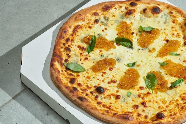 クリーミーなソース、缶詰の洋ナシ、玉ねぎ、溶けたモッツァレラチーズ、ゴルゴンゾーラ、クリスピーなリムが入ったおいしいピザ。ハードライト。灰色の表面。