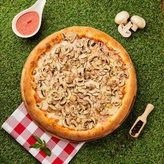 きのこと緑の草の上のハムとおいしいピザ