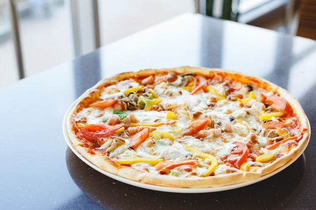 Delicious pizza with pepperoni and tomatoes dark table served in cafe or italian restaurant. hot pizza with mozzarella cheese.