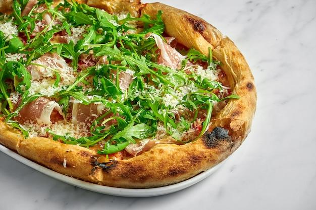 Вкусная пицца с прошутто, томатным соусом, пармезаном и рукколой на белой тарелке на белом мраморе