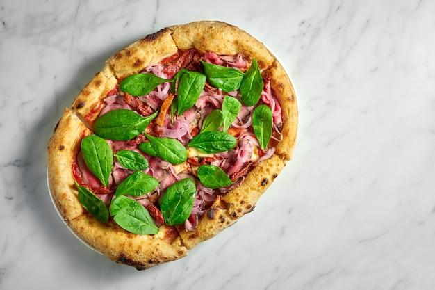 흰색 대리석 표면에 흰색 접시에 로스트 비프, 햇볕에 말린 토마토, 절인 양파, 치즈, 시금치와 함께 맛있는 피자