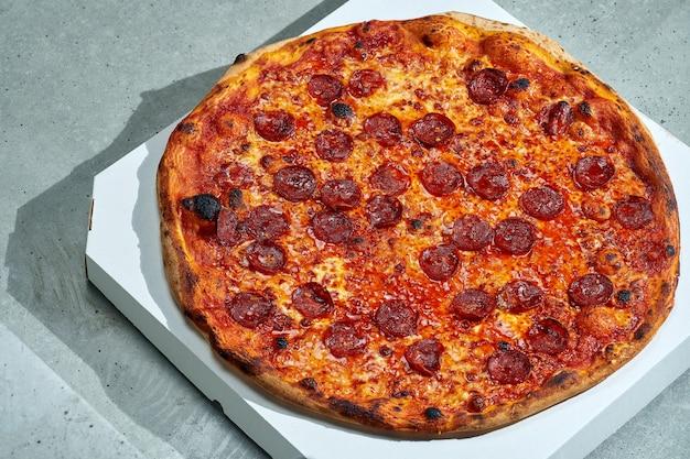 スパイシーなチョリソサラミとピーマン、トマトソースとサクサクしたサイドのおいしいピザ。ハードライト。灰色の表面 Premium写真