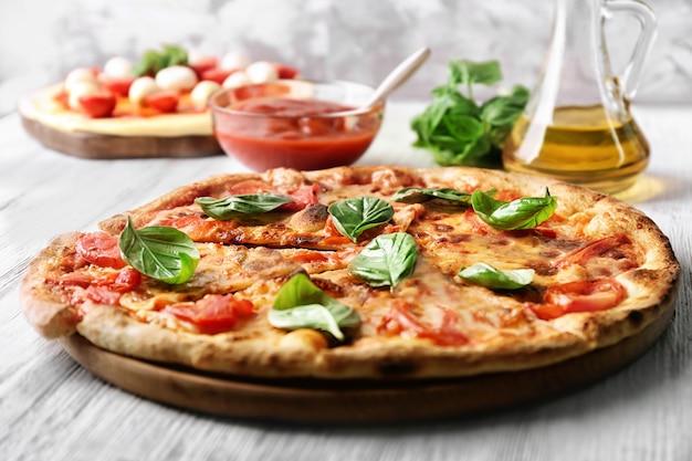 トマトと新鮮なバジルをキッチンテーブルに置いたおいしいピザ