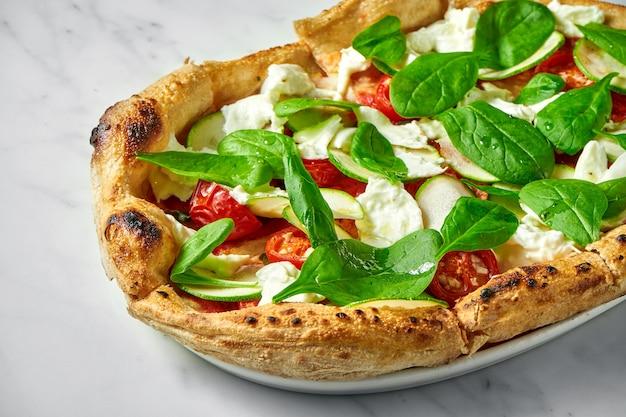 Вкусная пицца с кабачками, бурратой, вялеными помидорами и шпинатом на белой тарелке на белом мраморе