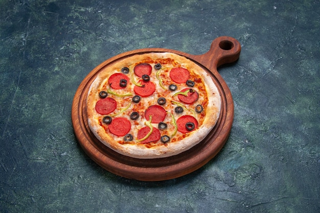 Delicious pizza on wooden cutting board on dark blue surface with free space in front shot