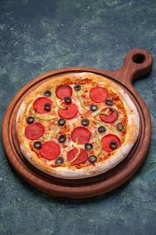 Pizza deliziosa su tagliere di legno su superficie blu scuro con spazio libero in vista verticale