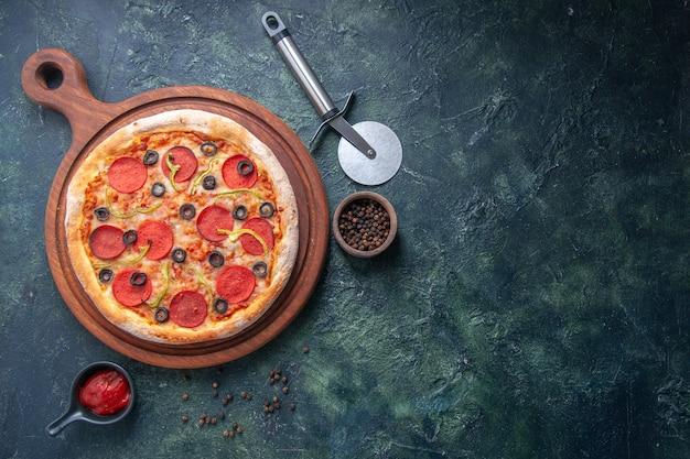 Pizza deliziosa su tagliere di legno e ketchup al pepe sul lato destro su superficie scura isolata