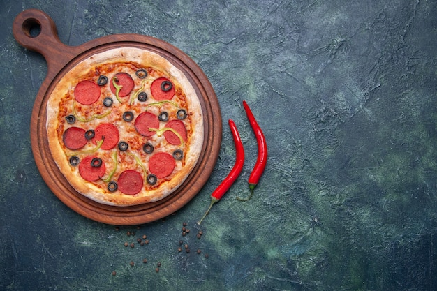 Delicious pizza on wooden cutting board and red peppers on isolated dark surface with free space