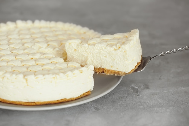 Delicious plain cheesecake on grey table