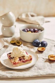 白いテーブルの上にクランブルとアイスクリームとおいしいプラムケーキ