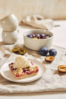 Delicious plum cake with crumble and ice cream on a white table