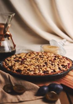 Вкусный сливовый пирог с кофе chemex и ингредиентами с тканью на деревянном столе с тканью
