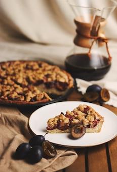 Chemexコーヒーと布で木製のテーブルに布で食材を使ったおいしいプラムパイ
