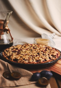Delicious  plum pie with chemex coffee and ingredients with fabric on a wooden table with fabric