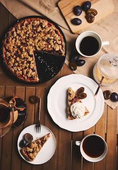 Deliziosa torta di prugne con caffè chemex e ingredienti con tessuto su un tavolo in legno con tessuto