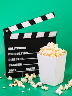 Delicious popcorn box with movie clapperboard