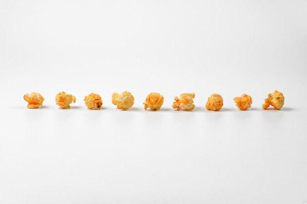 Delicious popcorn in a line on white