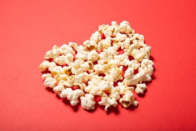 Вкусный попкорн на красном фоне. вид сверху, место для текста.
