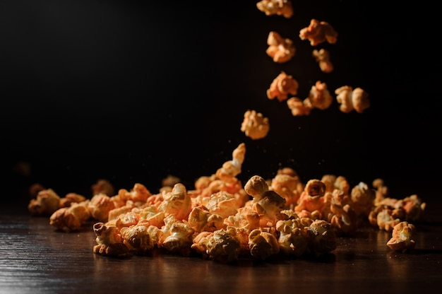 Delicious popcorn on the wooden table on the dark