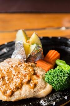 뜨거운 팬에 감자와 야채를 곁들인 맛있는 돼지 고기 스테이크
