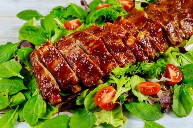 Вкусные свиные ребрышки с зеленым салатом и острым соусом барбекю