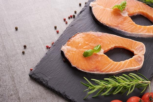 芳香性のハーブ、スパイス、野菜を使った新鮮なサケの切り身のおいしい部分-健康的な食べ物、食事、料理のコンセプト。準菜食主義の地中海式食事をきれいに食べるためのバランスの取れた栄養の概念。