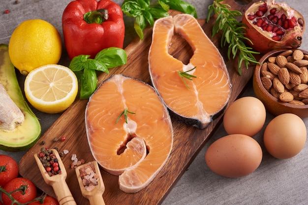 건강 식품, 다이어트 또는 요리 개념-향기로운 허브, 향신료와 야채와 신선한 연어 등심의 맛있는 부분. 깨끗한 식사 flexitarian 지중해 다이어트를위한 균형 잡힌 영양 개념.