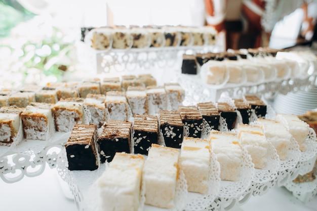 Вкусные порционные сладости подаются на слоистых подставках