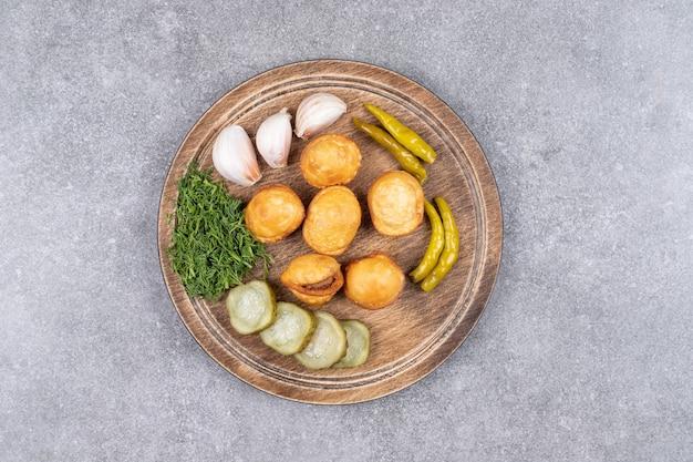 나무 보드에 통조림 된 야채와 함께 맛있는 감자 크로켓.