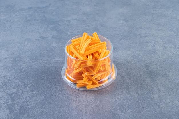 Deliziose patatine fritte su un bicchiere sulla superficie di marmo