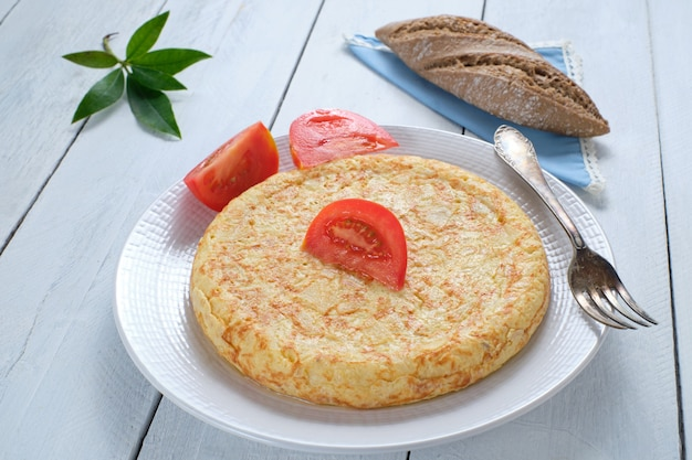 Delicious potato omelette, spanish omelette on a plate, with a tomato wedge