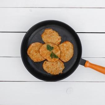 Вкусные картофельные оладьи на сковороде на белом деревянном столе