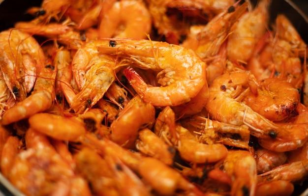 Вкусные приготовленные креветки на сковороде. жареные креветки с зеленью. морепродукты, моллюски. креветки креветки, обжаренные со специями на чугунной сковороде. фото крупным планом