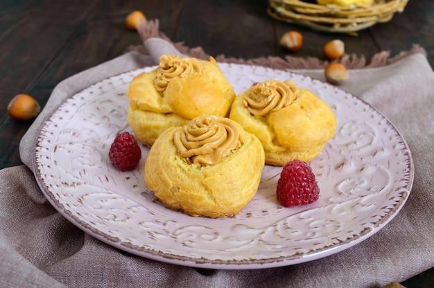 Вкусные профитроли с орехово-карамельным кремом на керамической тарелке
