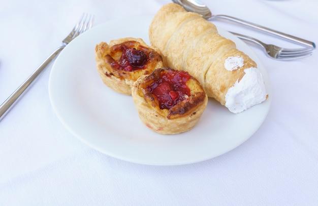 딸기 잼으로 가득 맛있는 퍼프 페이스 트리와 하얀 접시에 휘핑 크림 롤