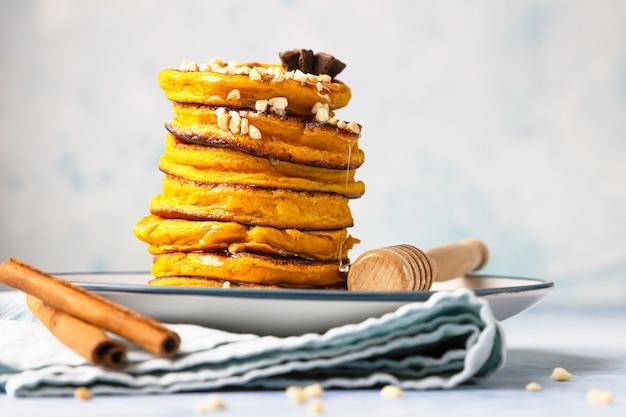 메이플 시럽 또는 꿀, 견과류와 함께 맛있는 호박 푹신한 팬케이크. 건강한 아침 식사. 가을 음식.