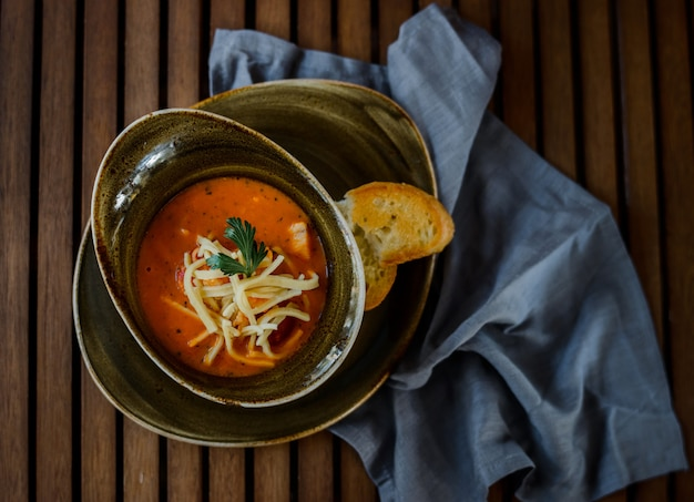 Delicious pumpkin soup with heavy cream on dark rustic wooden table