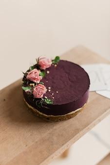 木製の背景においしい紫色のケーキ。花飾りのケーキ。ナチュラルケーキ