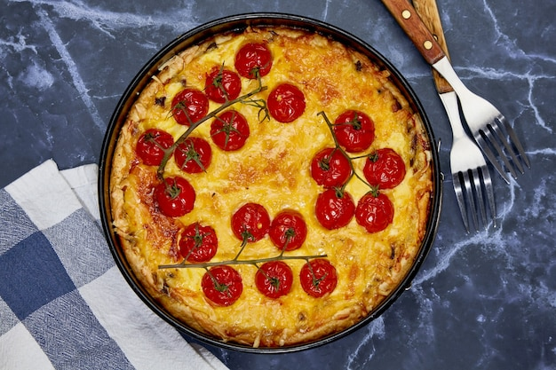 Delicious quiche with baked tomatoes on a branch and chicken, filled with cream, cheese and eggs.
