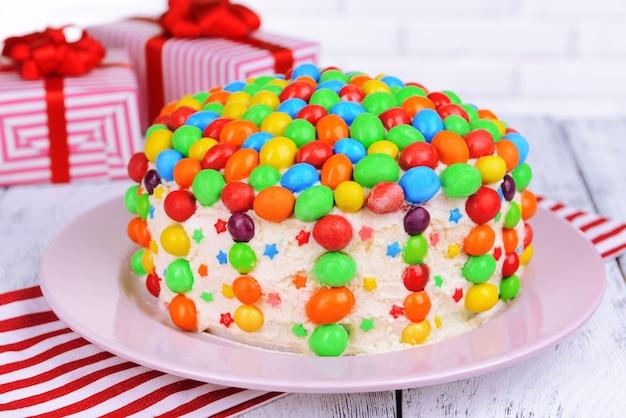 テーブルのクローズアップのプレート上のおいしいレインボーケーキ