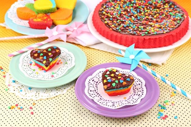 明るい背景に、プレート上のおいしいレインボーケーキ