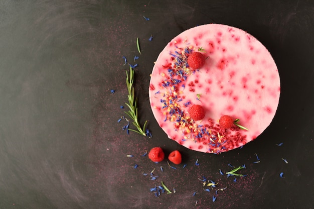 Delicious raspberry cake with fresh berries, rosemary and dry flowers. vegetarian, vegan food concept